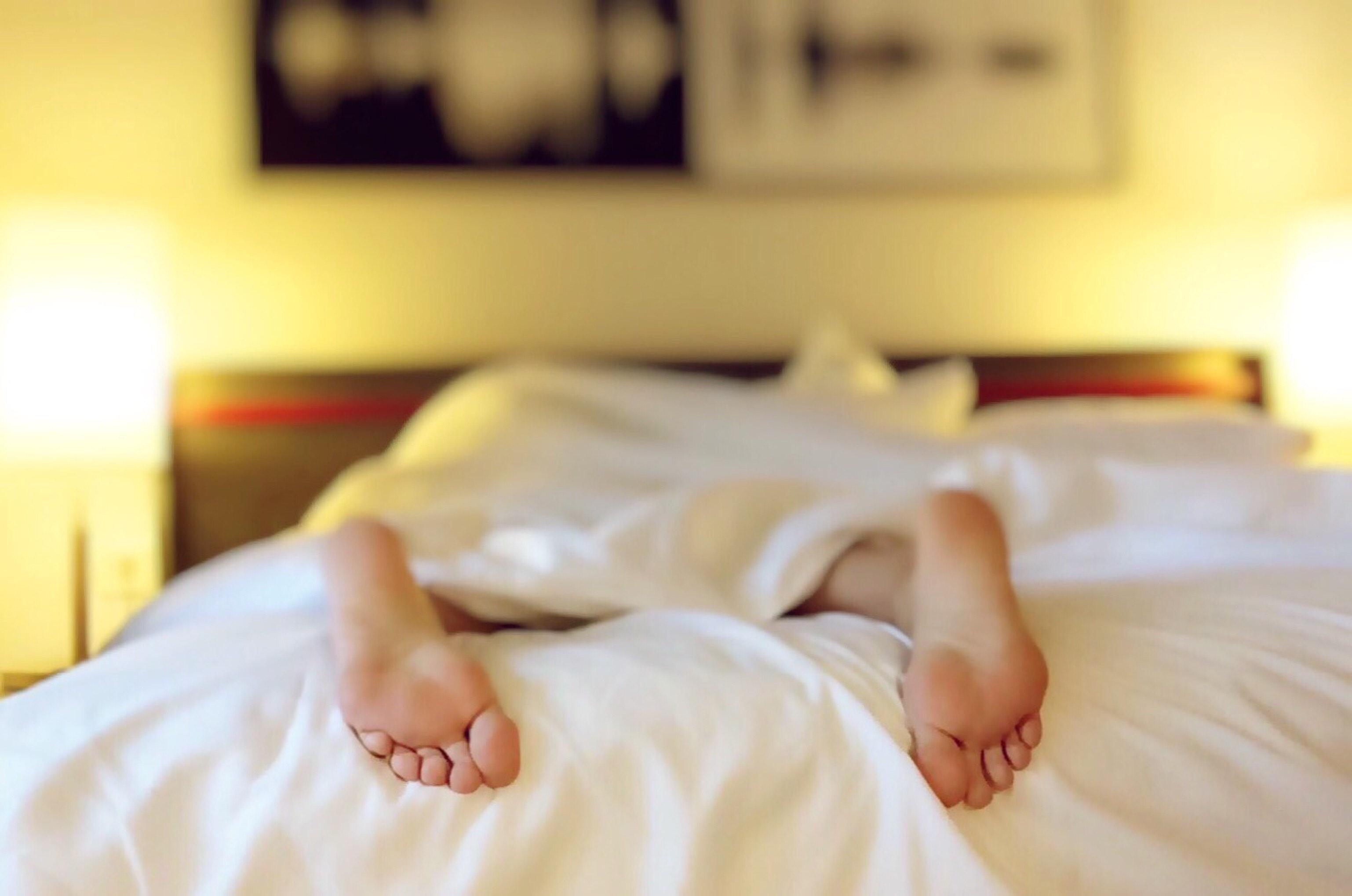 Pies sobre la cama