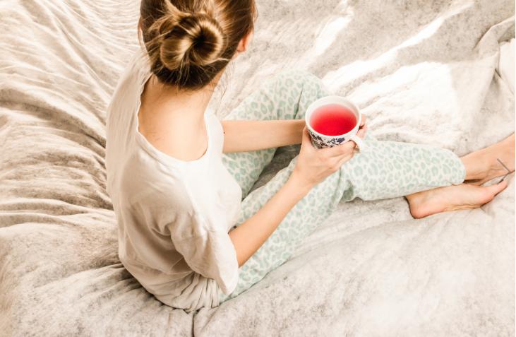 chica con un té sobre la cama