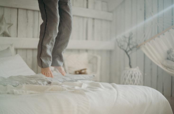 persona saltando en la cama